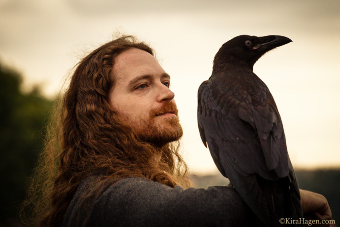 A man in Viking costume holds a young raven on his arm at  the third Times and Epochs Festival , Moscow Russia (Времена и Эпохи).